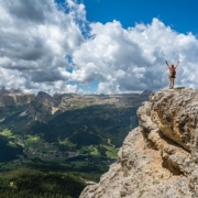 Woman on mountain top raises arms in victory